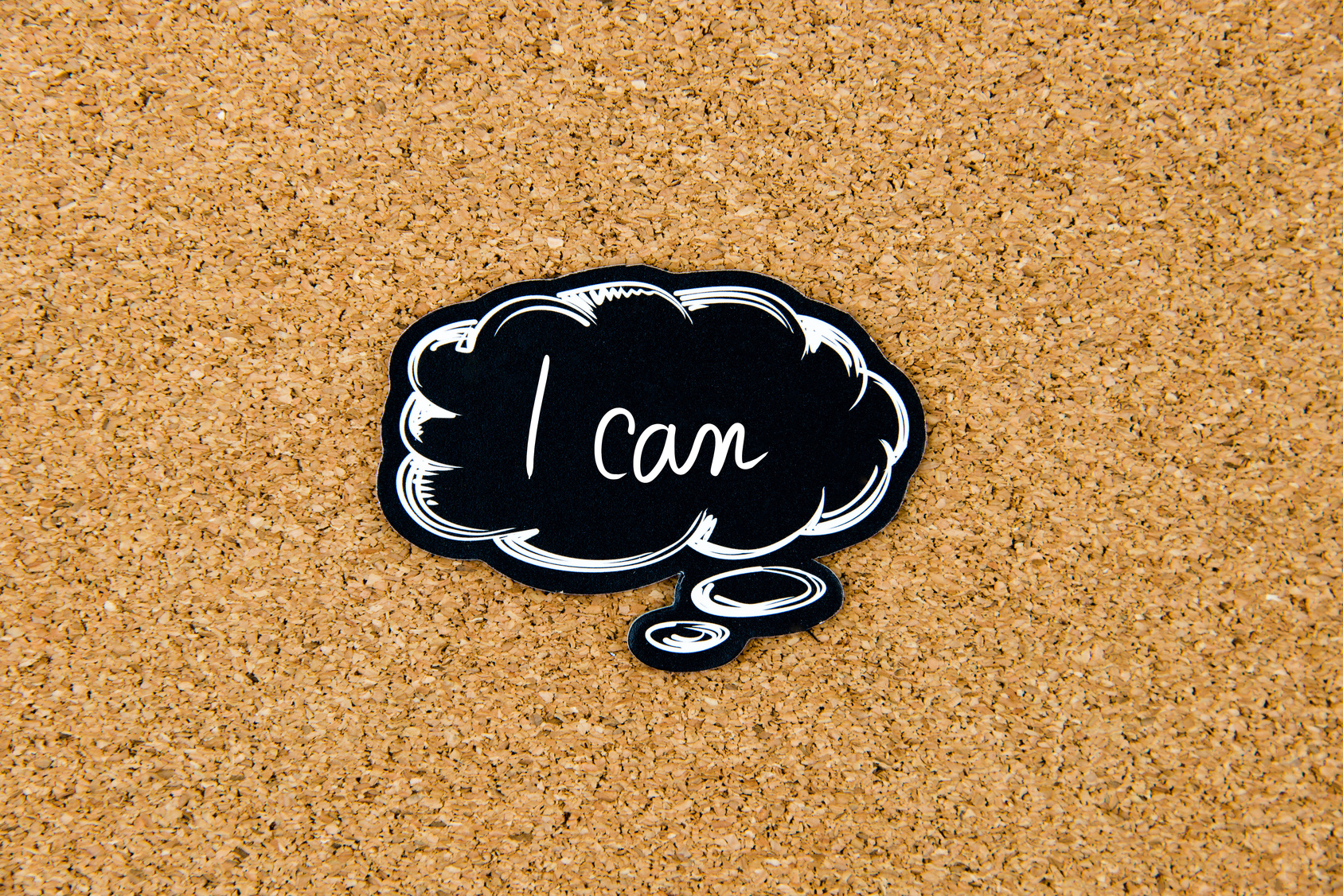 I CAN written on black thinking bubble over cork board background, copy space available